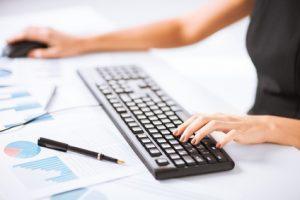 Assistant virtuel avec une main sur un clavier et une main sur la souris