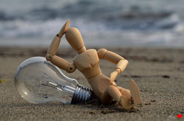 Petit bonhomme en bois contre une ampoule pour trouver une idée article blog