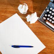 Photo redacteur personnel avec un bout de clavier, une feuille de papier, un stylo et des boulettes de papier